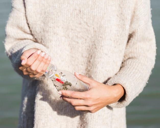 Donna che raccoglie plastica dalla spiaggia
