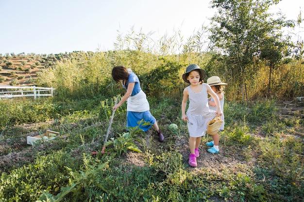 Donna che raccoglie verdure in campo con le sue figlie