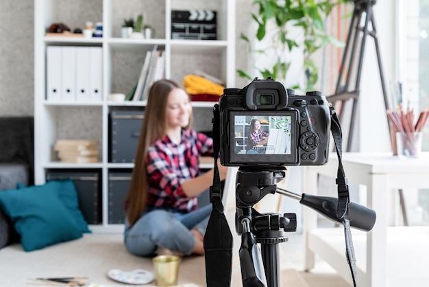 Donna che realizza un video per il suo blog sull'arte utilizzando una fotocamera digitale montata su treppiede
