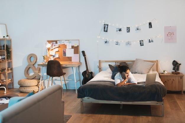 Donna che resta a letto e che osserva sul computer portatile