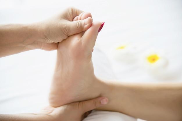Donna che riceve il servizio di massaggio ai piedi da massaggiatrice vicino a portata di mano e piedi - rilassarsi nel concetto di servizio di massaggio di massaggio del piede
