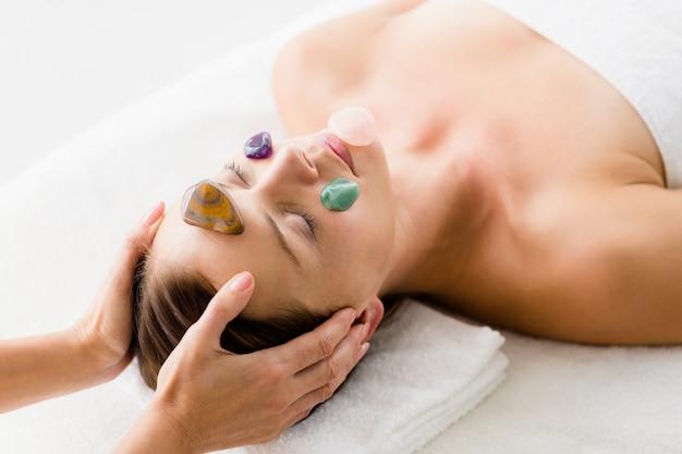 Donna che riceve massaggio facciale con pietre