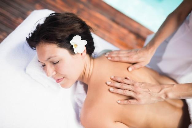 Donna che riceve un massaggio alla schiena da massaggiatore in una spa