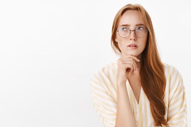 Donna che ricorda il programma durante la pianificazione della giornata lavorativa successiva in piedi concentrata e perplessa in occhiali alla moda guardando l'angolo in alto a sinistra pensieroso e concentrato facendo calcoli in mente