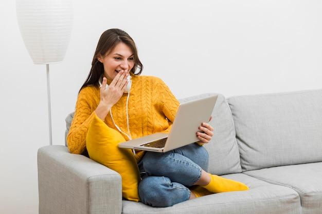 Donna che ride di qualcosa di divertente che ha visto sul suo computer portatile