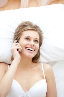 Donna che ride in biancheria intima parlando al telefono