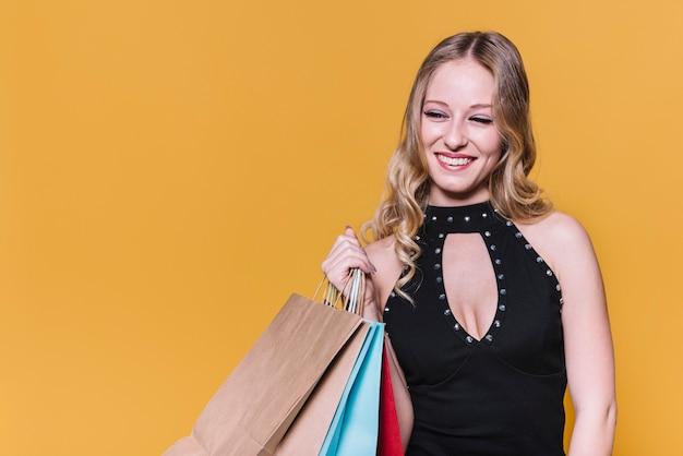 Donna che ride in vestito che tiene i sacchetti della spesa