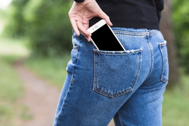 Donna che rimuove lo smartphone dalla tasca dei jeans blu