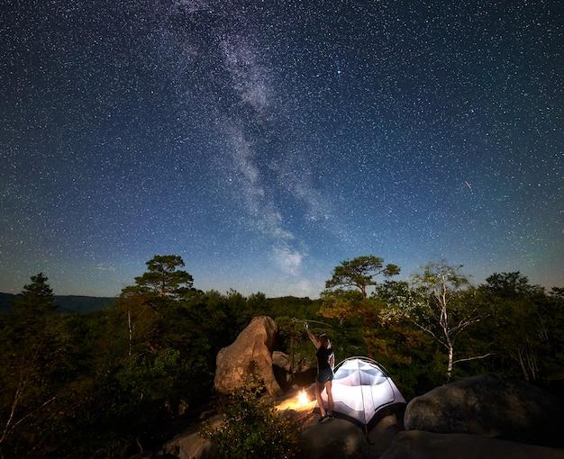 Donna che riposa accanto al campo, falò e tenda turistica di notte
