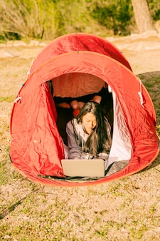 Donna che riposa in tenda e usando il portatile