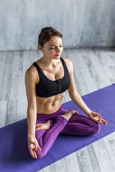 Donna che riposa in una posa di yoga del loto