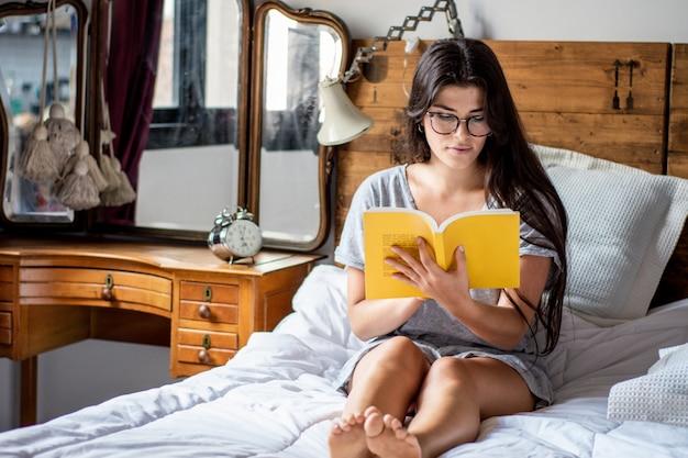 Donna che risiede nel letto e nel libro di lettura