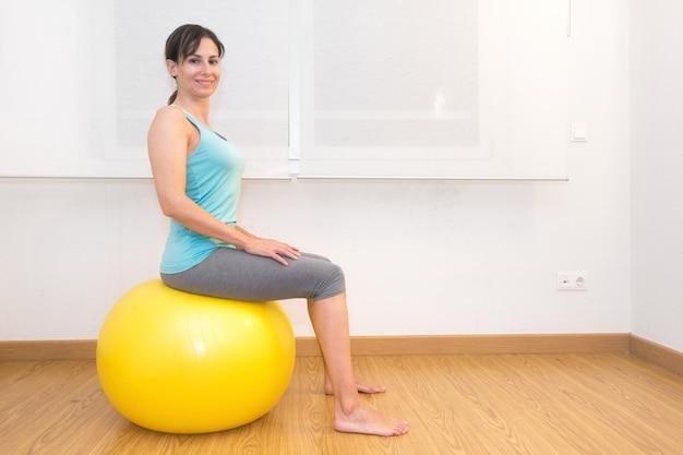 Donna che risolve con la palla di esercizio in palestra. donna di pilates che fa le esercitazioni nella stanza di allenamento della palestra con la palla di forma fisica.