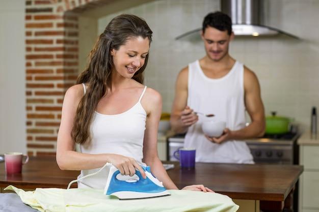Donna che riveste di ferro una camicia mentre uomo che mangia prima colazione nel fondo