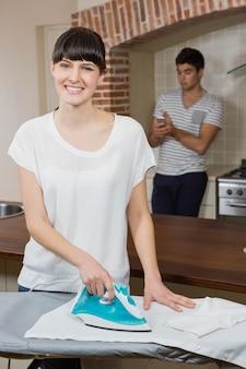 Donna che riveste di ferro una camicia mentre uomo che per mezzo del telefono cellulare