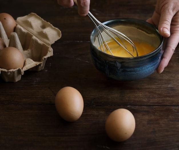 Donna che sbatte l'idea di ricetta di fotografia dell'alimento delle uova
