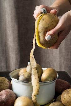 Donna che sbuccia patate crude