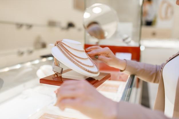 Donna che sceglie collana d'oro in vetrina in gioielleria. persona di sesso femminile l'acquisto di decorazioni in oro in gioielleria