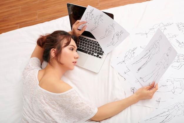 Donna che sceglie i disegni per la nuova collezione