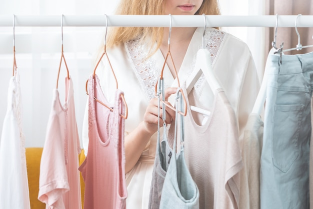 Donna che sceglie i vestiti nel guardaroba di casa