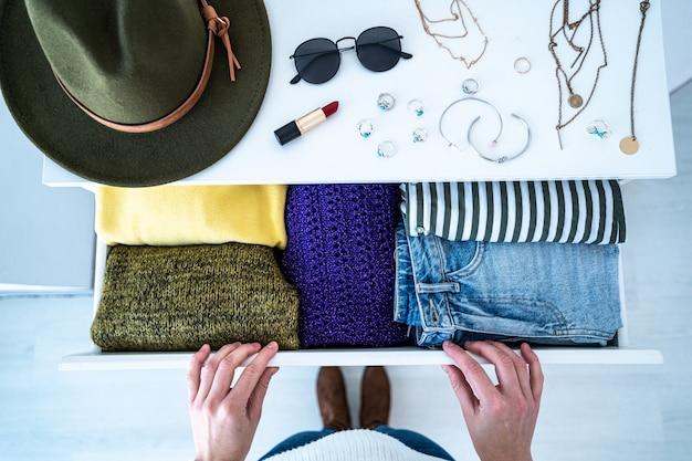 Donna che sceglie il vestito dalla cassettiera con eleganti abiti alla moda casual, roba per la casa e accessori femminili. vista dall'alto.