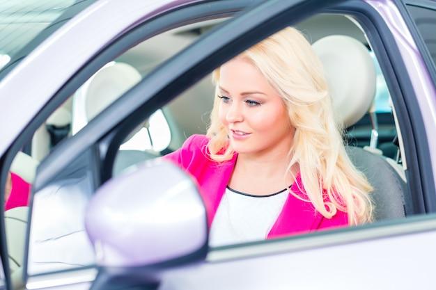 Donna che sceglie l'automobile per l'acquisto nella gestione commerciale