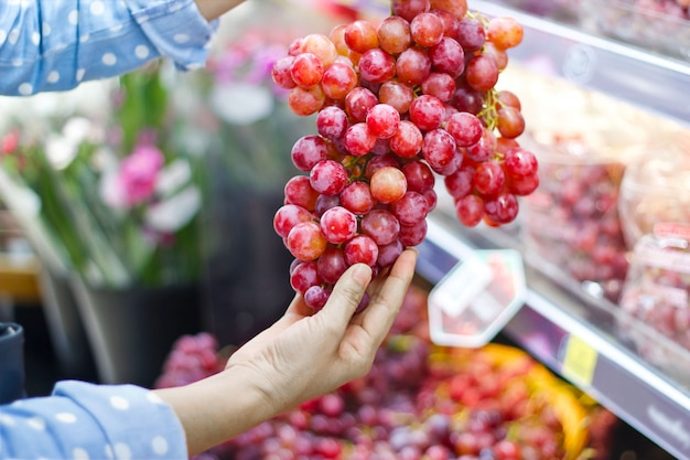 Donna che sceglie l'uva rossa fresca del mazzo per comprare nel supermercato