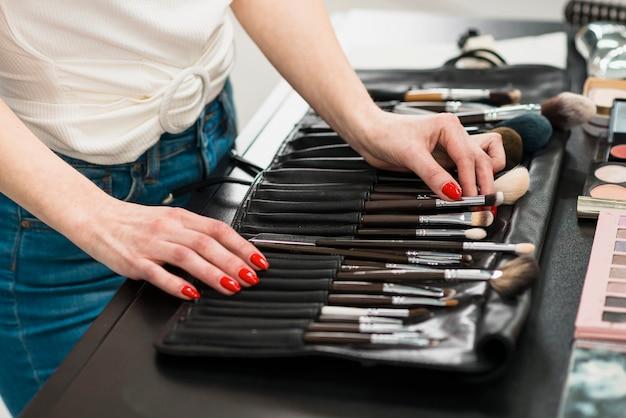 Donna che sceglie la spazzola di trucco dall'insieme