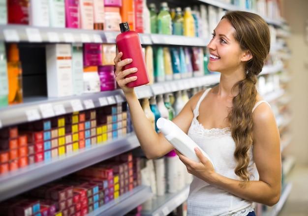 Donna che sceglie lo shampoo al negozio