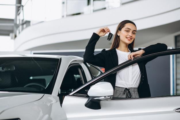 Donna che sceglie un'automobile in una sala d'esposizione dell'automobile