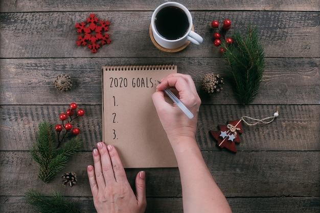 Donna che scrive gli obiettivi 2020 in taccuino con le decorazioni di festa sulla tavola di legno