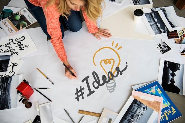 Donna che scrive hashtag idee su una carta