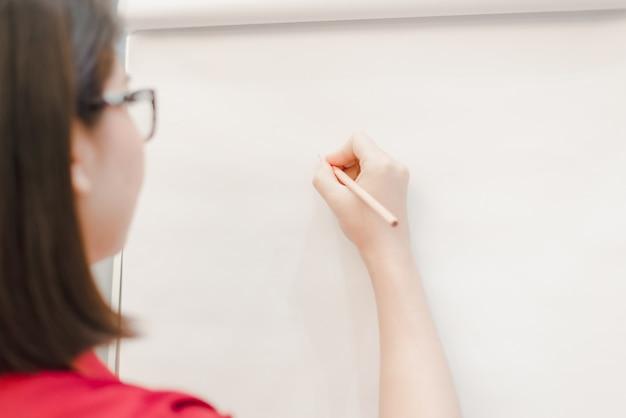 Donna che scrive su carta lavagna
