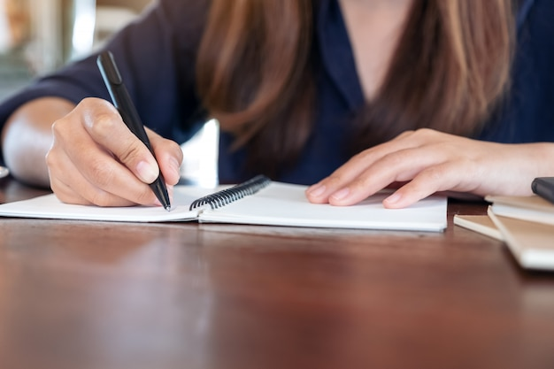 Donna che scrive sul taccuino in bianco sul tavolo nella caffetteria