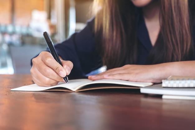Donna che scrive sul taccuino in bianco sulla tavola di legno