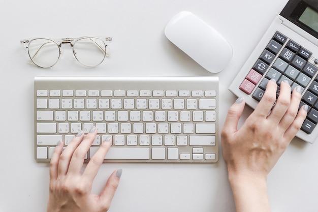 Donna che scrive sulla tastiera, utilizzando calcolatrice, occhiali e mouse