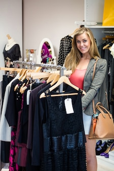 Donna che seleziona un vestito mentre acquistando per i vestiti