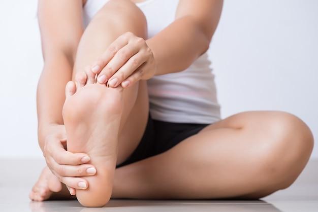 Donna che sente dolore al piede a casa. sanità e concetto medico.