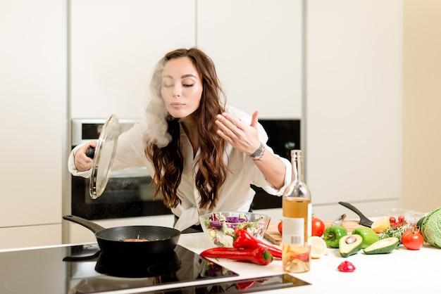 Donna che sente l'odore del vapore dalla padella e cucina la bistecca di pesce fresco con vino bianco e verdure in cucina