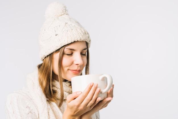 Donna che sente l'odore della bevanda calda