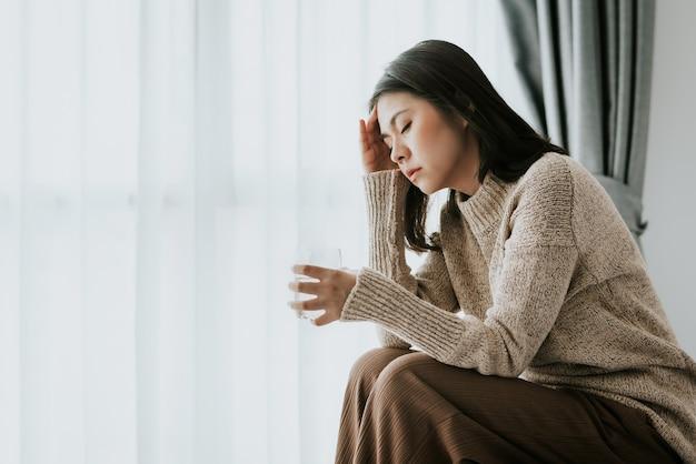 Donna che sente mal di testa da influenza e raffreddore