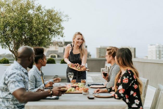 Donna che serve barbecue vegano ai suoi amici