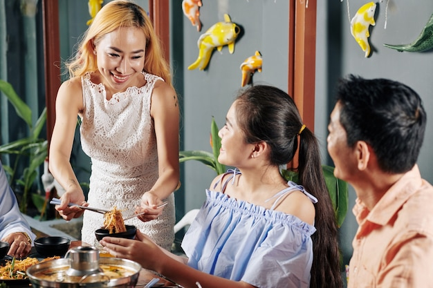 Donna che serve noodle piccanti di soba
