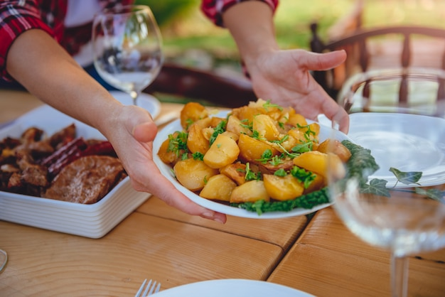 Donna che serve patate arrosto sul tavolo da pranzo