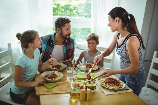 Donna che serve un pasto alla sua famiglia