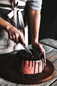 Donna che serve una deliziosa torta in fetta