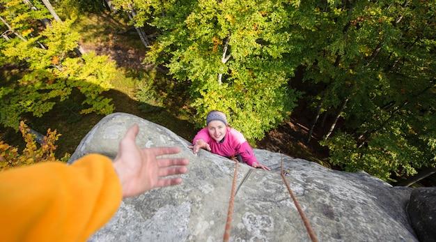 Donna che si arrampica nella natura sul grande masso