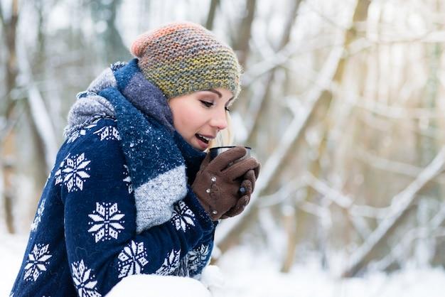 Donna che si congela in una fredda giornata invernale riscaldandosi con il caldo