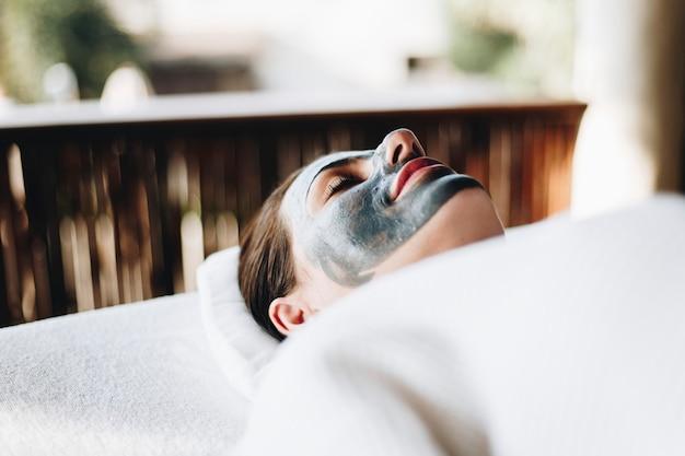 Donna che si distende con una maschera facciale presso la spa