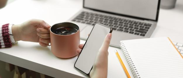 Donna che si distende dal lavoro con mock up smartphone e caffè ghiacciato sul tavolo bianco